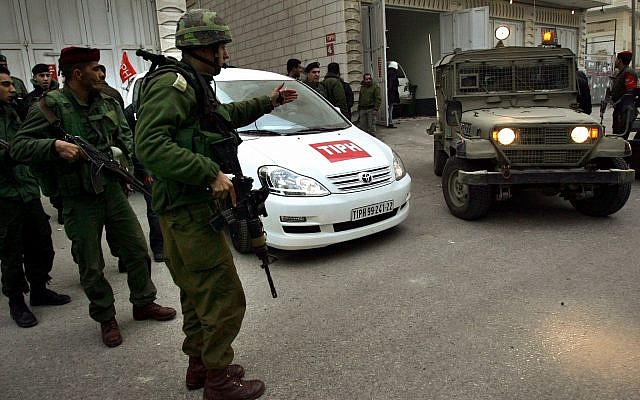 Soldiers stand near a car used by members of the TIPH Temporary International Presence in Hebron