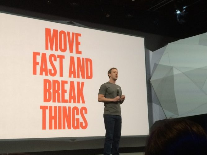 Facebook CEO Mark Zuckerberg speaks at a 2014 San Francisco event in front of a screen showing one of the tech giant's early mottos,