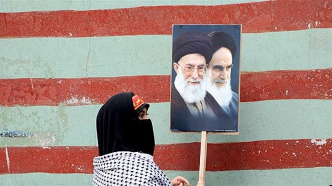 An Iranian woman displays the images of Leader of the Islamic Revolution Ayatollah Seyyed Ali Khamenei and Founder of the Islamic Republic Ayatollah Ruhollah Khomeini outside the wall of the former U.S. Embassy in Tehran. (File photo)
