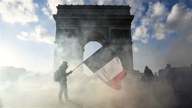 In this file photo taken on March 16, 2019, a protester holds a French national flag as he walks among the tear gas smoke past the Arc de Triomphe on the Place de l'Etoile in Paris. (Photo by AFP), From InText
