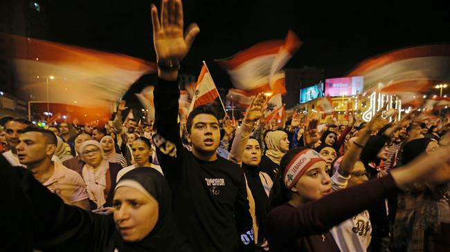 Lebanese protesters wave flags and shout slogans during an anti-government demonstration at al-Nour Square in the northern port city of Tripoli on November 2, 2019.
