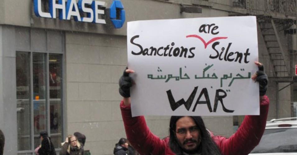 Protester's sign decries sanctions,