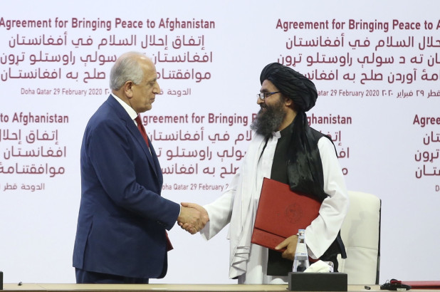 US Special Representative for Afghanistan Reconciliation Zalmay Khalilzad (L) and Taliban co-founder Mullah Abdul Ghani Baradar (R) shake hands