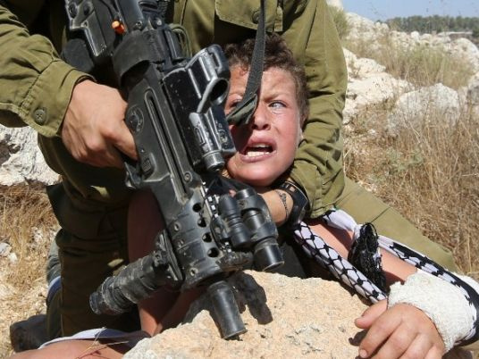 Armed to the teeth would be this:  Israeli soldier terrorizing Palestinian child.
